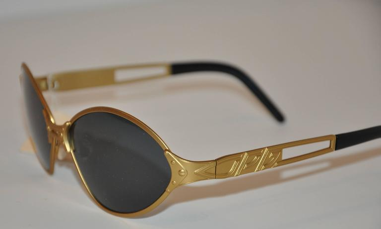 Jean Paul Gaultier wonderfully detailed gold tone sunglasses are detailed with micro-studs on the center-front as well as the corners. The arms are accented with the signature etched nameplate as well. Tips are finished with black lucite. The front