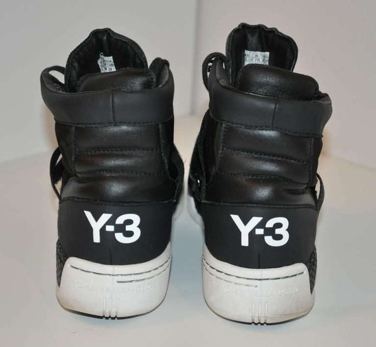 "Yohji Yamamoto's wonderfully detailed black high-top lace-up sneakers has the option of an ""Strap-Over"" Velcose in front as well as a ""Hook-Up"" for the top row near the top. The soles has a slight wedge. Size is 8/US, 41/French, 7 1/2/UK. Length"
