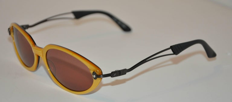 """Jean Paul Gaultier wonderfully detailed golden lucite sunglasses are finished with black lucite interior. The arms are black hardware with black lucite tips. The length across the front measures 5 3/4"""", height is 1 1/2"""", arms are 5"""