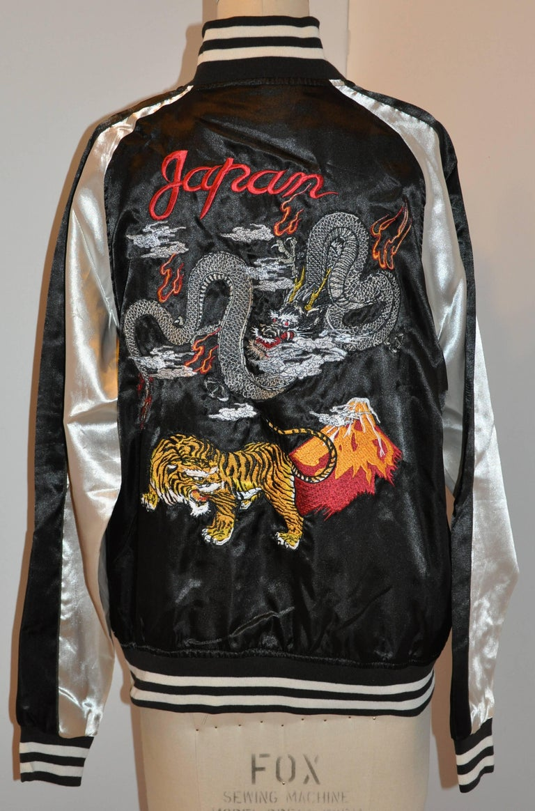 """This wonderful Japanese ivory and black fully lined zippered bomber-style jacket is embroidered with Dragons and a tiger, finished with the words """"Japan"""" in back. The collar as well as the hem is accented with a three-inch stripe"""