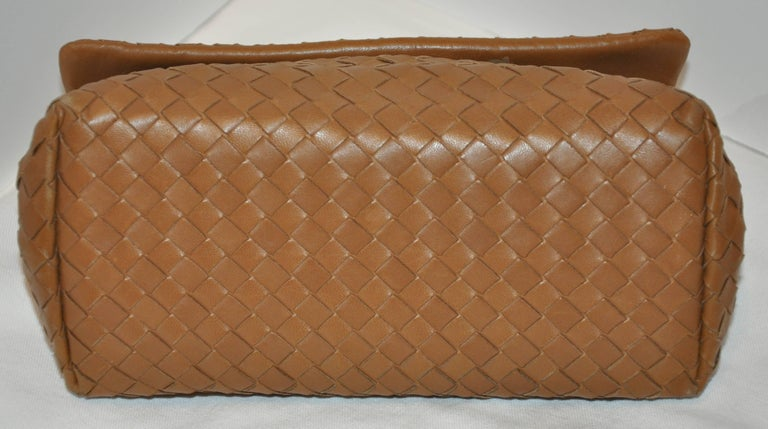 Bottega Veneta wonderfully elegant beige lambskin woven clutch has a two-sectional interior including a zippered compartment in-between. The flap-over closes with a magnetic center. The interior of the flap is slightly discolored (please