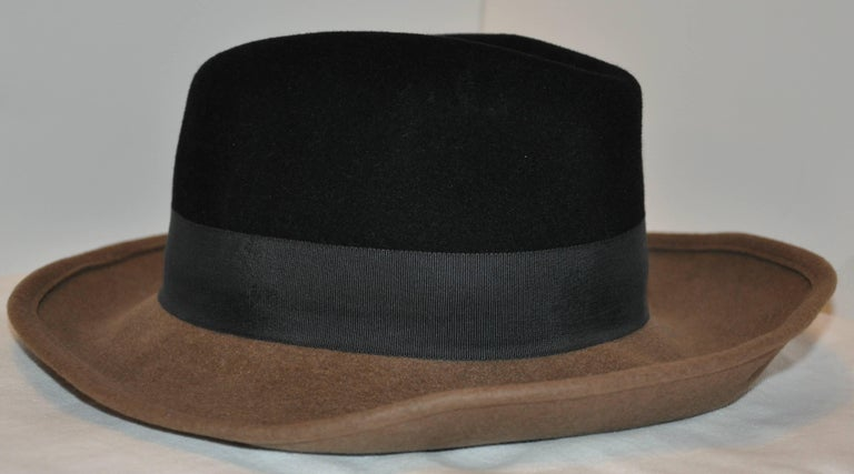 Adolfo wonderful whimsical combination of warm brown and black wool felt accented with a black silk cord band wide brim hat measures 4 3/4 inches in height. The interior circumference measures 22 1/4 inches, the exterior wide brim