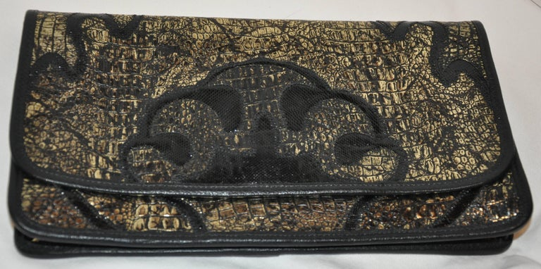 Carlos Falchi wonderful black and metallic gold embossed alligator calfskin clutch has the option to use as a shoulder bag as well if desired. Black lizard skin is detailed on both the front as well as the back. All edges are finished with