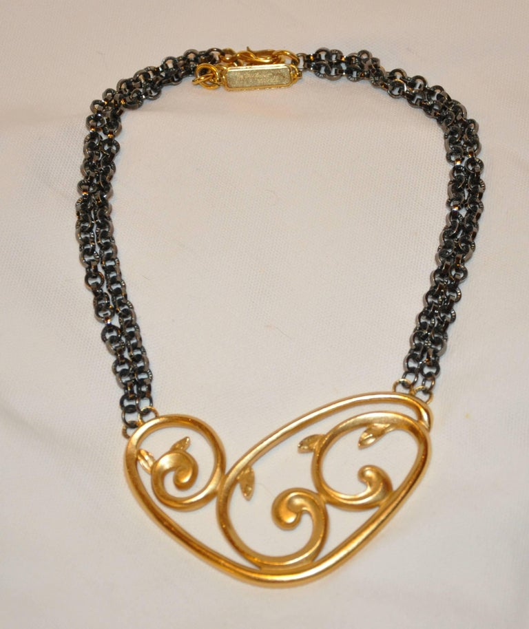 "Yves Saint Laurent wonderfully elegant ""Limited Edition"" #331/500 two tier chain-link gunmetal accented with a huge pendant of polished gilded gold vermeil hardware of ""Swirls"". The adjustable chain-link necklace measures"