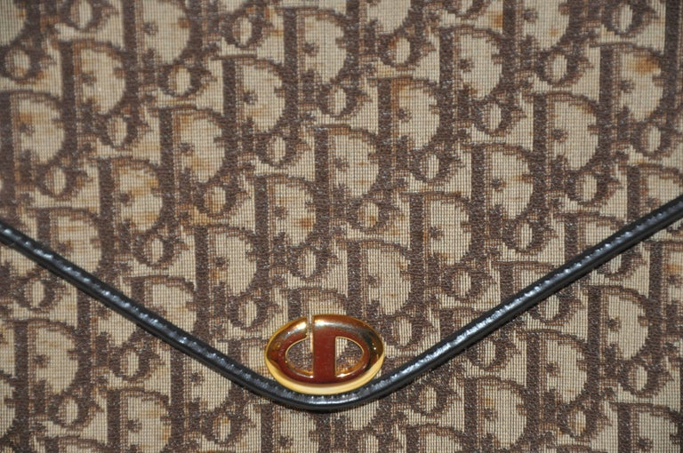 Christian Dior signature classic brown canvas accented with coco brown calfskin edges logo clutch measures 10 inches in length. The height measures 7 1/2 inches, flap on front is 5 1/2 inches. The interior is lined with matching coco brown