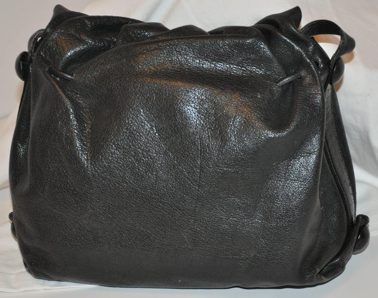 Carlos Falchi wonderful signature large black textured buffalo skin shoulder bag detailed with his renowned hand-etched patches on the front flap. The front flap measures 11 inches in length. The shoulder straps measures 1 inch in width and