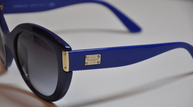 Gianni Versace wonderfully wicked thick bold Lapis-shade sunglasses accented with gilded gold hardware and studs. The arms are detailed with the signature name etched into the gilded gold hardware plate. The front measures 5 7/8 inches