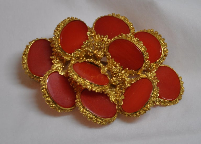 Wonderfully detailed etched 18k gilded yellow gold brooch and optional hat pin is accented with bursts of natural coral. The back is detailed with a safety pin to help secure this wonderfully elegant brooch in place. The brooch measures 2