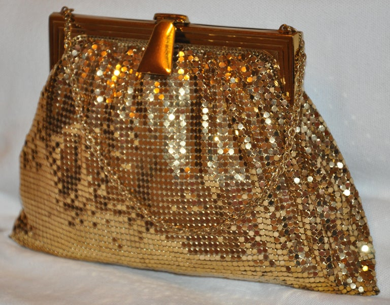 Whiting & Davis wonderfully elegant gilded gold hardware mesh evening bag is accented with a matching gilded gold hardware chain strap which measures 5 inches in height. The length measures 8 inches along the bottom and 5 inches along the