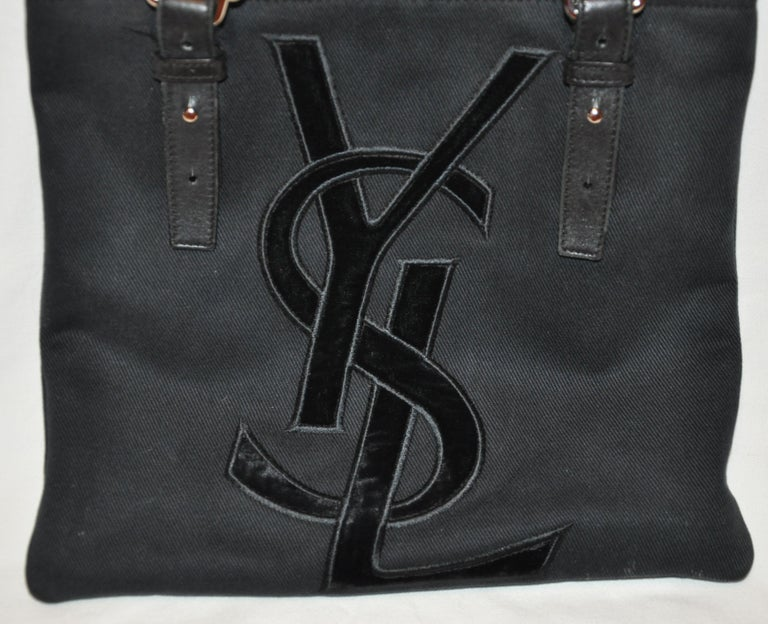 Yves Saint Laurent wonderful signature velvet monogram front adjustable double handle tote bag is detailed with adjustable handles measuring from 10 1/2 to 13 1/2 inches. The handles are combined with black calfskin as well as black canvas