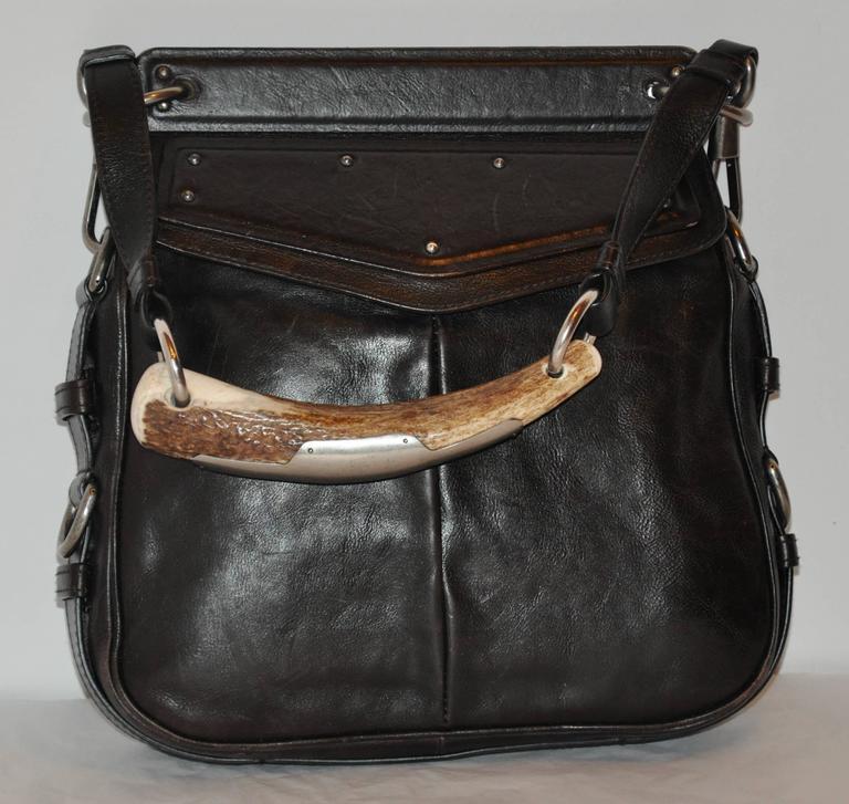 Yves Saint Laurent detailed black calfskin handbag features a large