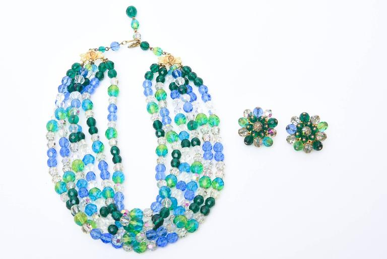 The colors of the sea in alternating glass beads of blues and greens make up this signed Elsa Schiaparelli vintage necklace. There are 6 wide strands on each side of luscious colored glass beads and matching  clip on cluster earrings. Sold as a set