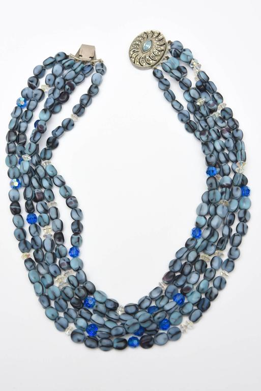 Beautiful hues of steel gray to gray blues to blues to royal to light blue make up this 5 strand Murano glass bead necklace. There are clear glass beads interspersed. They almost look like special pebbles of glass. This is a wearable lovely necklace