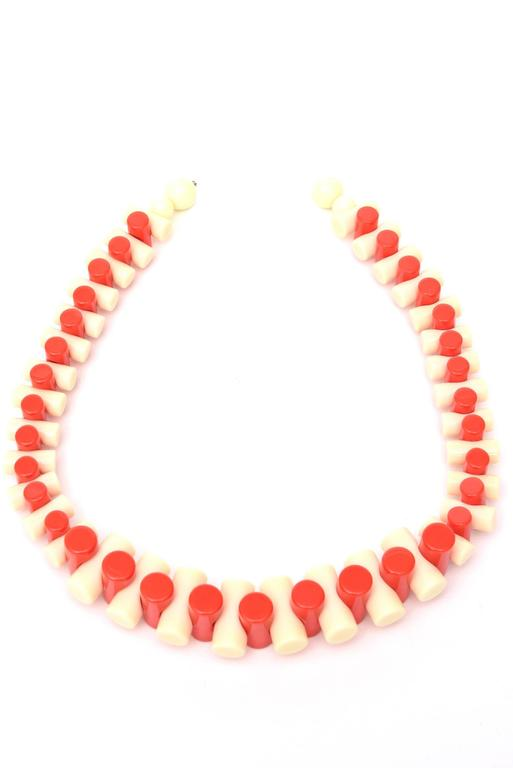 Alternating colors of orange and creme resin make up this sculptural necklace that makes a statement. It graduates in size of the tubular formed resin. It is french from the 90's. Perfect for resort wear and  summer 2021 This is also wonderful for