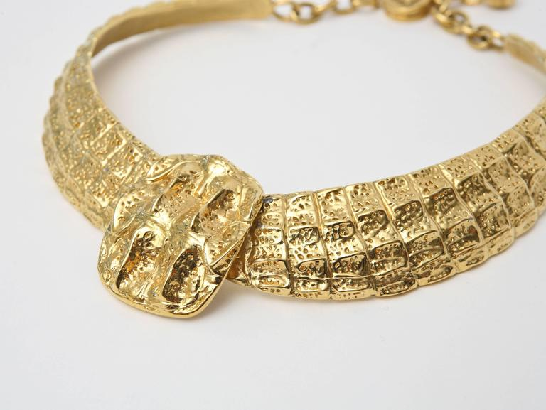This dramatic, sculptural and stunning gold plated signed Yves Saint Laurent collar necklace has some dimension and texture. It is tagged YSL Paris. It can be sized for different neck widths from the closure and rings. The center sculptural pendant