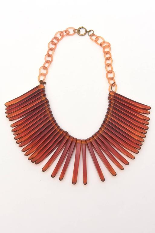 This very in vogue collar choker vintage resin necklace looks like fringe. It is tortoise like in color with resin links in a lighter amber color. It lays beautifully on the neck. A great piece any wardrobe. Fringe is in, hot and back! It is from