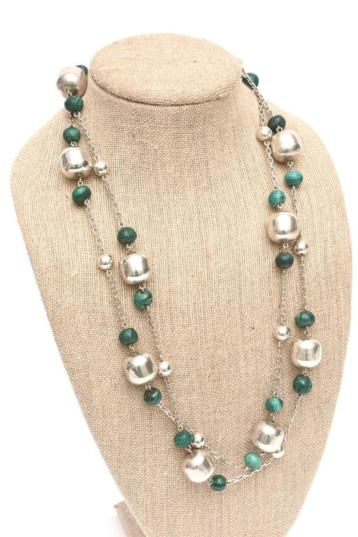 This gorgeous sterling silver and malachite strand necklace can be worn st different lengths when doubled or as one long dramatic strand. The sterling barrel beads are large and compliment the malachite rounded beads with an open chain effect. This