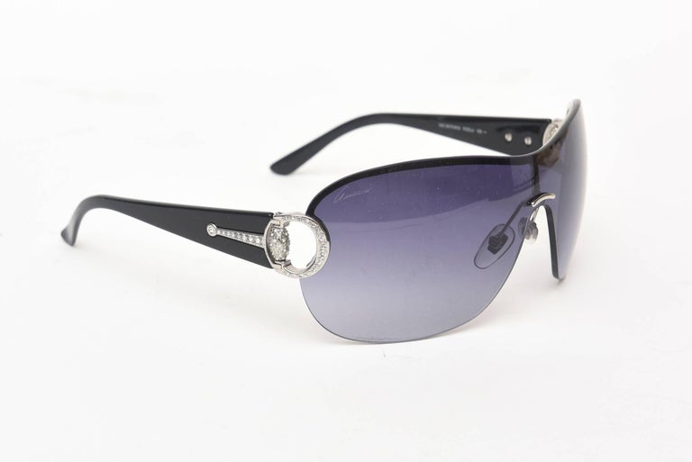 This Gucci sunglasses has never been worn and has the original papers , case and box. They are dramatic with rhinestones on the side. They are in aviator form with a blue tinted lens.
