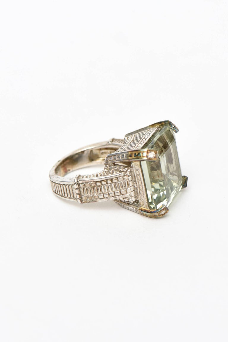 This classic and gorgeous hallmarked Judith Ripka ring has a green amethyst and 4 tiny diamond on all 4 sides in a sterling silver and 18K white gold  setting. The diamonds are tiny points. It is contemporary and was done most likely about 12 years