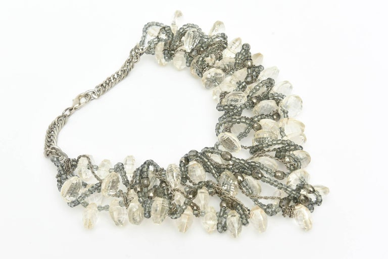 This most arresting and unusual bib chunky multi strand necklace is from the 80's. It is faceted clear lucite interspersed with  intertwined chain, gray beads and silver. It is a conversation piece and lays beautifully on the neck in dramatic and