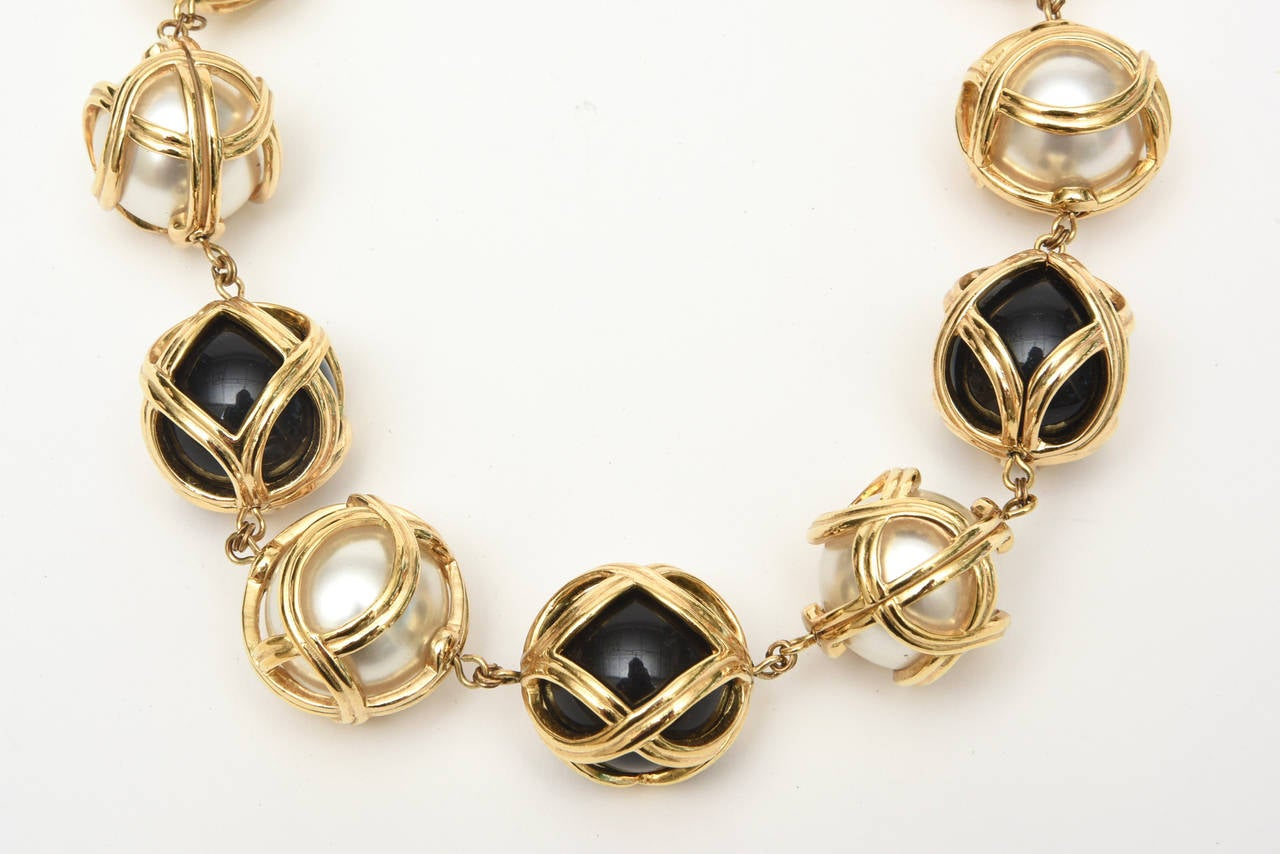 This fabulous Christian Dior runway fabulous ball necklace has black resin and faux pearl balls encased in a crisscross cage form. This is a very unusual and captivating necklace. It is gold plated. This is classic and elegant. It is a special Dior