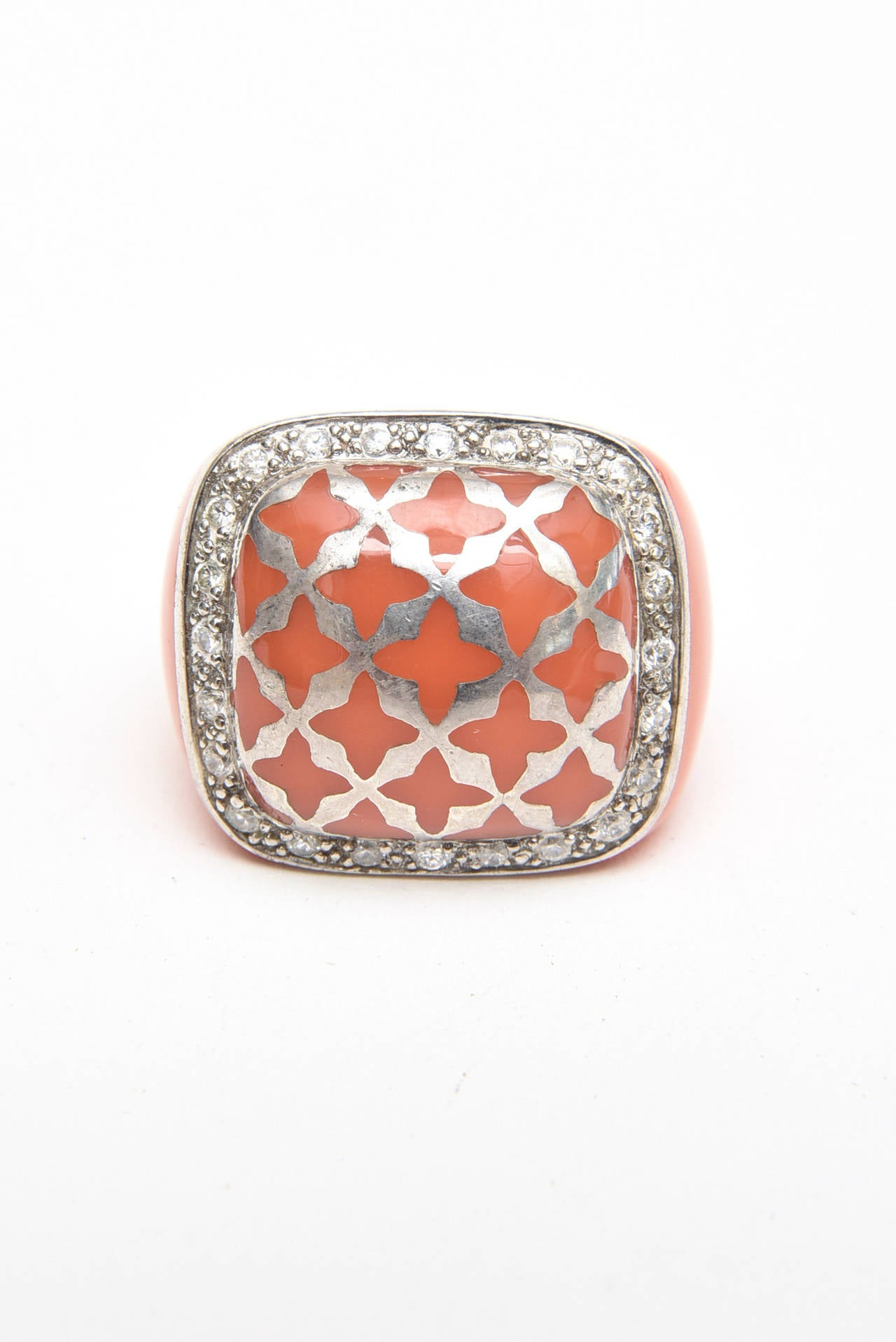 The luscious coral hermes orange color of the resin set against the sterling silver is dramatic and show stopping. There is a diamond like lattice pattern of sterling silver. This French dome ring is fabulous and unusual. it is by Angelique de Paris