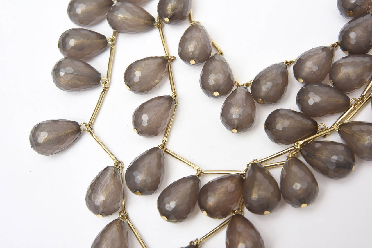 Three strands of gilt metal and grey resin coffee bean shaped beads make up this lovely and arresting necklace. They are like almond shaped resin dropped on a chain. It has a great presence and lays well on the neck and chest. It looks