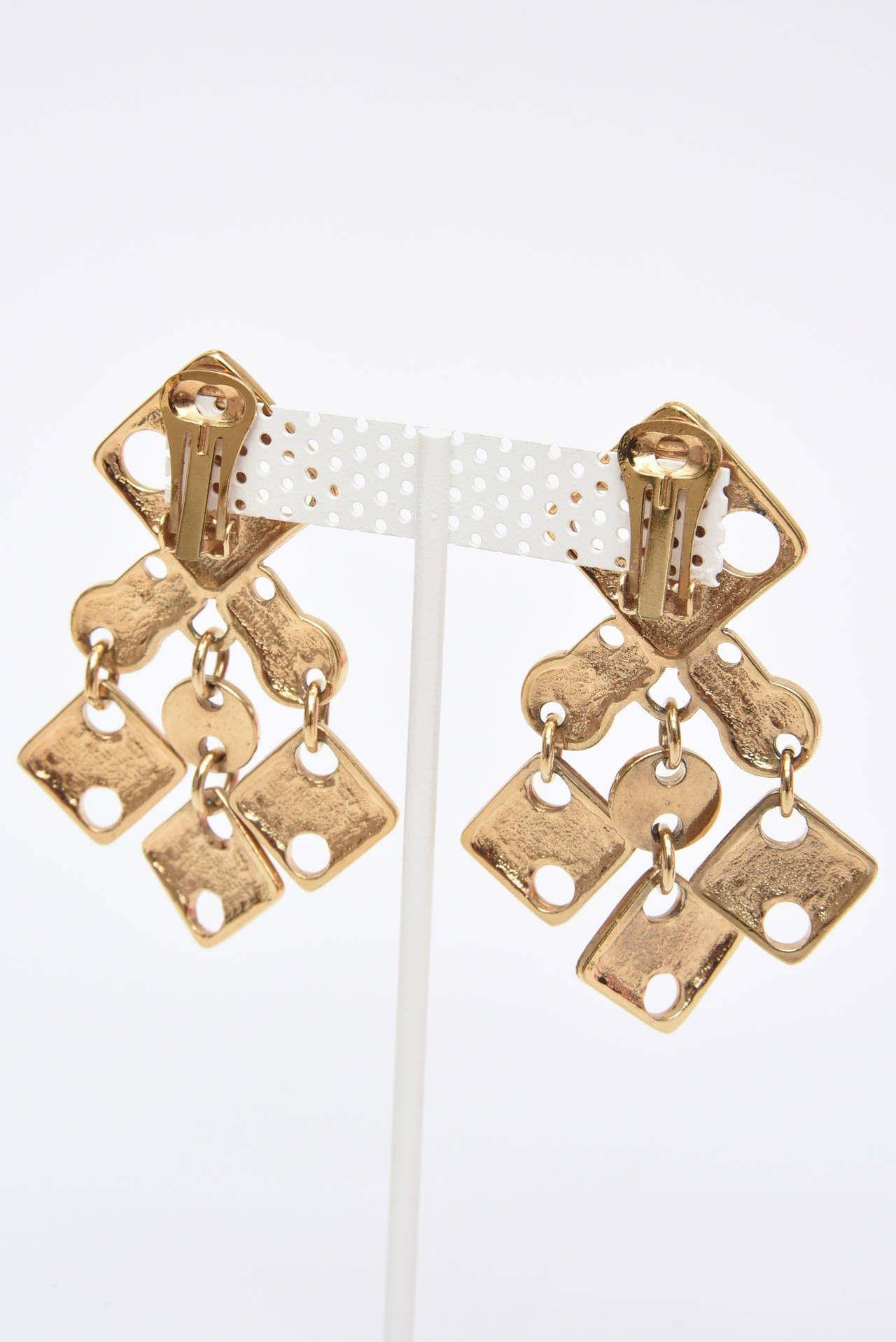 These fabulous and amazing signed French Paco Rabanne modernist dangle sculptural earrings are so au courant now as they were then in the 60's. The  geometric cutout forms and angles will forever be in stye. They are gold plated brass and have some