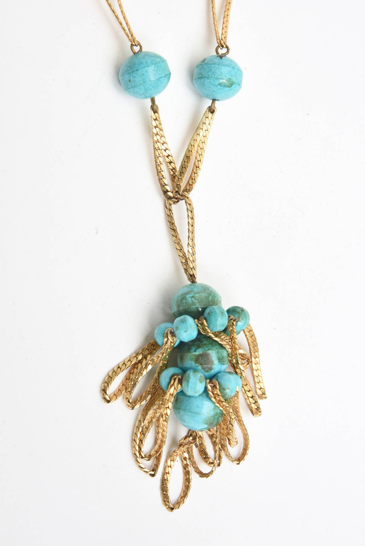 This gorgeous and versatile vintage long necklace is signed Hattie Carnegie. It is from the 70's. Turquoise and braided gold tone tassled necklace is so it now! The dangling braided gold parts interspersed with turquoise clusters is hip and so