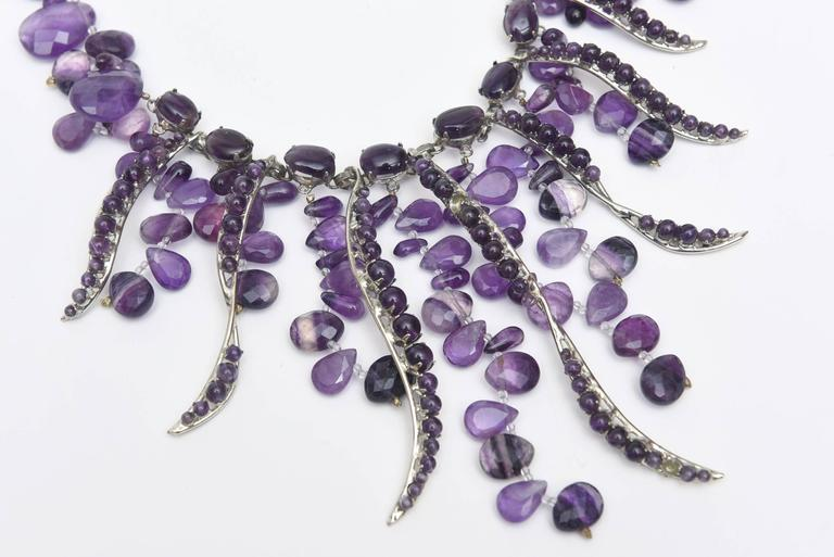This dramatic and theatrical cascading amethyst and silver bib necklace looks stunning on. It is signed by Siman Tu. His work is in the category of jewelry designer Iranj Monji. SIman Tu is a NYC based well known semi precious stone jewelry designer