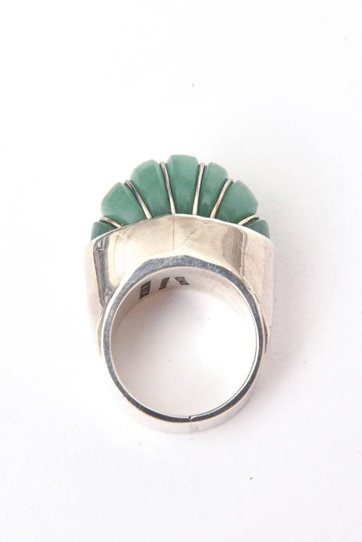 Unique petals of Jade on this ring sit high against the Sterling Silver.  It is sculptural and dimensional. The ring has height on your finger and sits high. The ring size is 8.25. It can always be sized to your specifications at your end. It is all