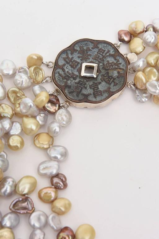 """Cultured Freshwater baroque pearls of multi-color make up this lovely multi 5 strand necklace with a  with a beautiful Sterling Silver Sculptural large clasp.  It is 8.5"""" H /L x 1.5"""" D each strand."""
