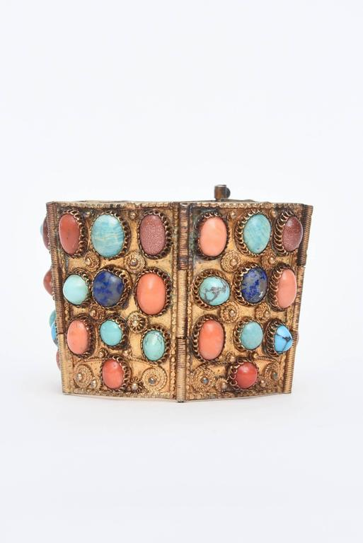 This dramatic and gorgeous cuff bracelet has Egyptian Revival meets Byzantine  influences. It is period from the late 30's and has real stones of different coral, turquoise, lapis and Chinese sand stone. It is set against vermeil and has a beautiful