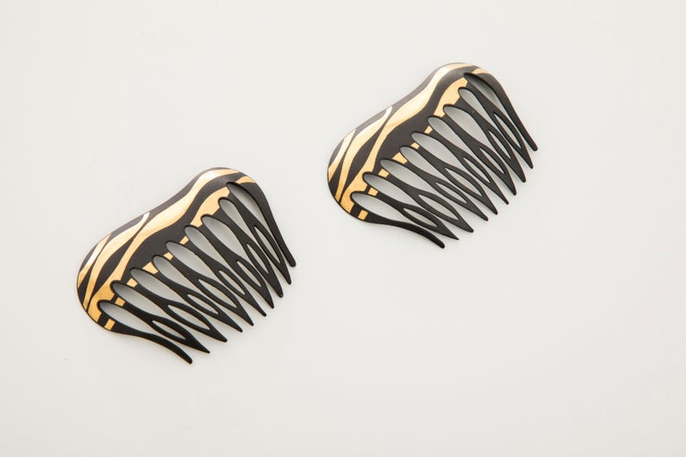Angela Cummings for Tiffany & Co., Circa: 1970's a pair of Damascene lacquered iron and gold hair combs of striped design, in 22k.   W 2.38 in. W 60.46 mm
