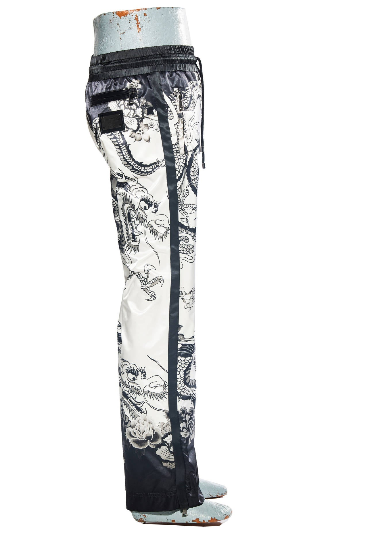 "Dolce and Gabbana, Spring-Summer 2009 printed satin pants with dragon motif, zippers at ankles, silver-tone logo plate at back, three zip pockets, drawstring waist and front fly closure.  Retail $1745  Waist 31"", Hip 38"", Rise 10.5"", Inseam 33"", Leg"