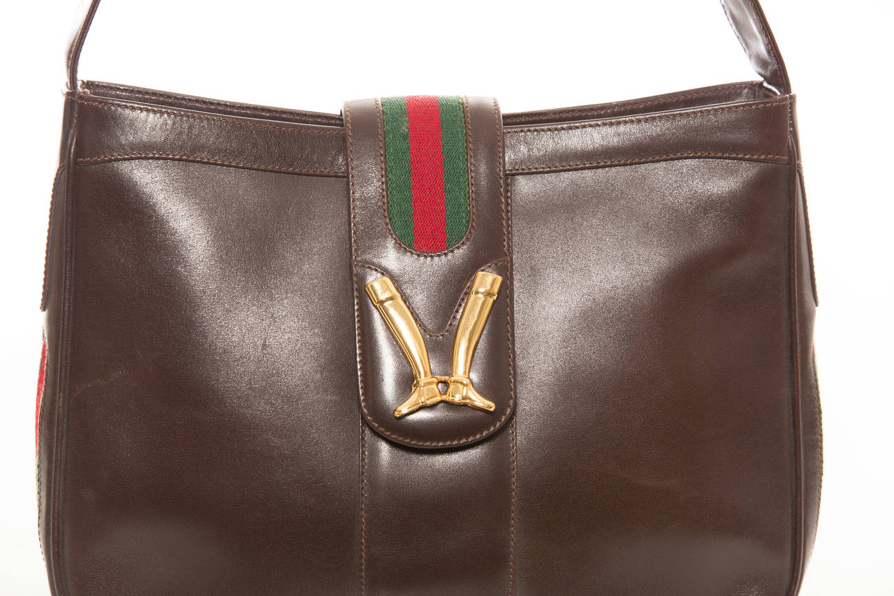 Gucci, circa 1970's brown leather handbag with gold plated  equestrian boots on the fold over adjustable shoulder strap,tan leather interior with one pocket and gold zipper Gucci pull.  Includes original dust bag and Gucci box.  Height 9, Width 12,