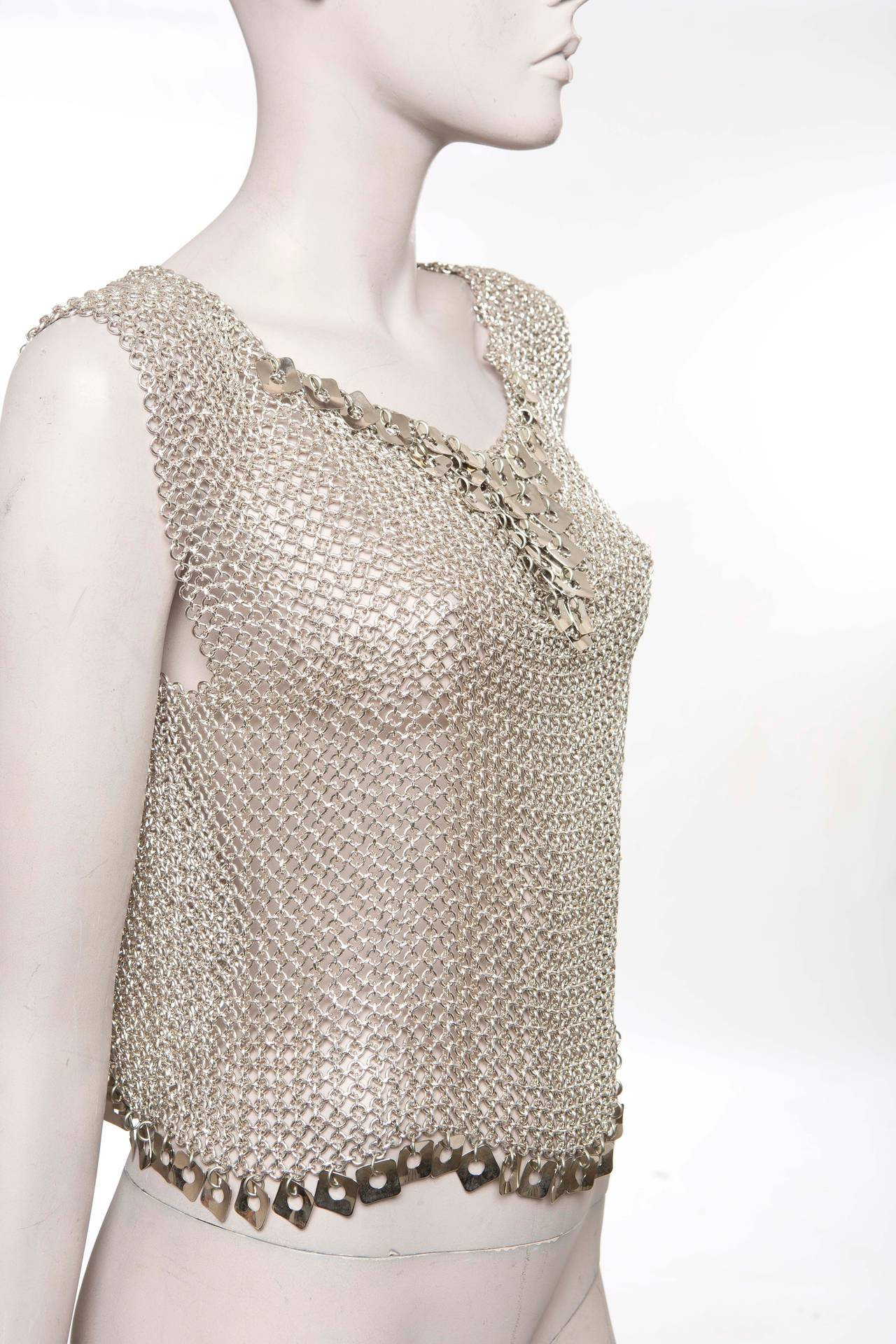 Paco Rabanne, circa 1970's chain-mail top with charm accented yoke and asymmetrical scalloped hemline featuring charm embellishments.