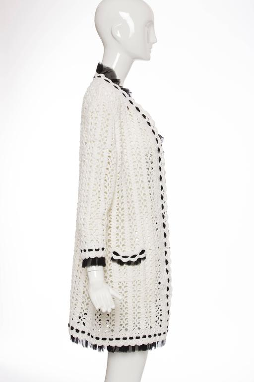 """Chanel, Spring 2005, ivory long sleeve crochet knit cardigan with black silk chiffon trim throughout and dual patch pockets at front.  FR. 42 US. 10   Bust 39"""", Waist 38"""", Length 31"""" Fabric Content: 81% Nylon, 18% Cotton, 1% Elastane;"""