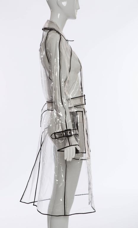 Prada, Autumn - Winter 2002-3, transparent PVC rain coat with pointed collar, long sleeves, dual zip pockets at sides, belted waist, contrasting black trim throughout and snap closures at front.   Exhibited at the Met's Spring 2012 Costume