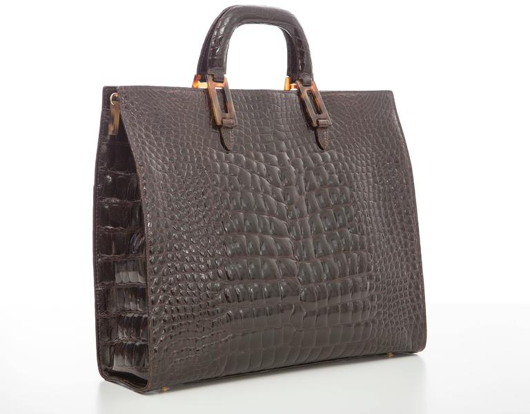 Lana Marks chocolate brown alligator tote with gold-tone hardware, dual flat top handles, black leather lining, three pockets at interior walls; one with zip closure and zip closure at top.