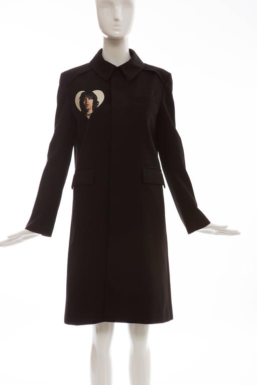 Undercover by Jun Takahashi, Spring-Summer 2016, black, wool, cotton coat with Rolling Stone graphic print throughout, pointed collar, three slit pockets at bodice, concealed button closures at center front and fully lined.  US. 2 Bust: 38