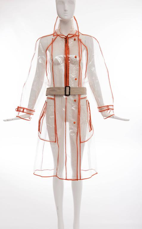 Prada, Autumn - Winter 2002-3, transparent PVC rain coat with pointed collar, long sleeves, dual zip pockets at sides, belted waist, contrasting orange trim throughout and snap and zip closures at front.    IT. 42 US. 6  Bust: 46 Waist: 46 Shoulder: