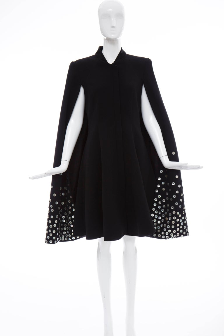 Gareth Pugh, Spring-Summer 2015 black dress with standing collar, cape overlay, mother of pearl button accents throughout, dual slit pockets at sides and concealed zip closure at front.   GB. 12 US. 10 IT. 44  Bust: 36, Waist 32, Hip 48, Length