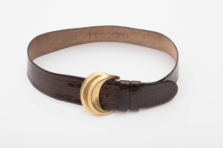 Donna Karan, Circa 1980's chocolate brown Caiman Crocodile waist belt with tonal stitching and Robert Lee Morris gold-tone buckle with peg-in-hole closure  Size: Large  Length Min: 31, Max 34, Width 2.5