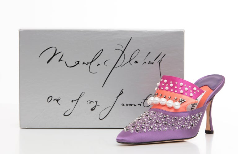 "Manolo Blahnik, Circa 1995 lavender, coral and pink silk satin mules with pointed toes, faux pearl embellishments throughout and covered heels. Includes box.  EU. 38 US. 8  Heels: 4  Exhibited: "" The Art of Shoes"" exhibition."