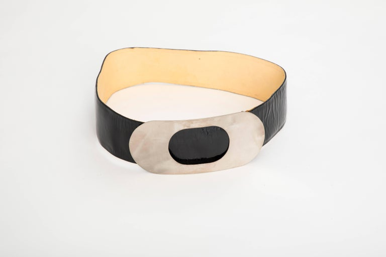 """Pierre Cardin, Circa 1960's black patent leather belt with oval circle buckle in silver tone, embossed designer branding in gold to the interiors and """"Made in France Expressly for Bonwit Teller"""".  31"""