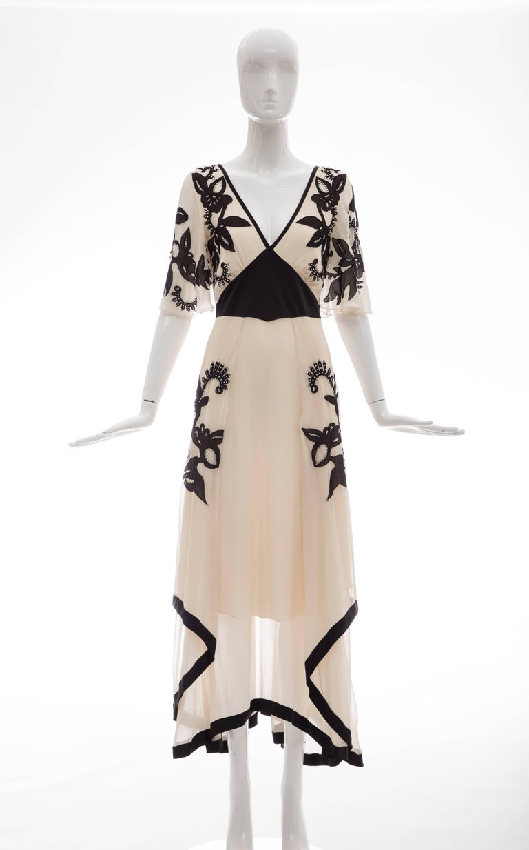 Temperley London, Runway Spring 2005, cream silk chiffon evening dress with black floral embroidered silk chiffon and prong-set crystals, black silk charmeuse waist and trim with handkerchief hem, bell sleeves, side zip and fully lined in silk.  UK.