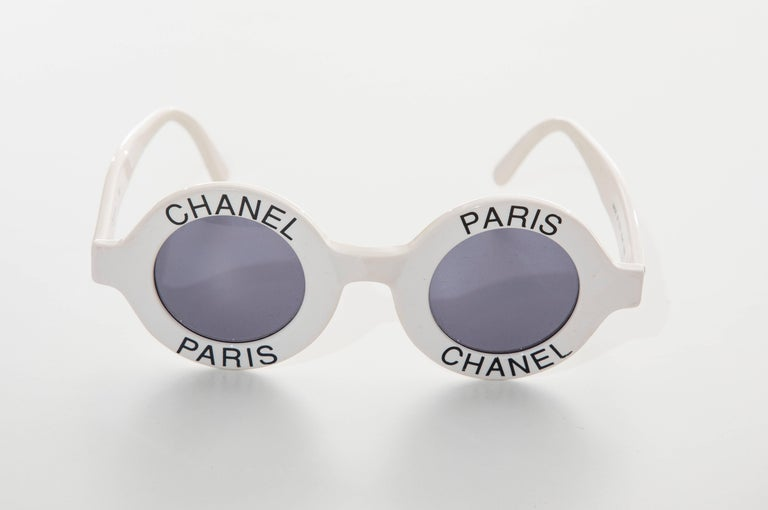 Chanel, Spring-Summer 1993 runway, logo, round white sunglasses with tinted lenses, black Chanel Paris accents at frames and interlocking CC detailing at temples. Includes case.    (page 162, CHANEL CATWALK, Patrick Mauries, Thames &