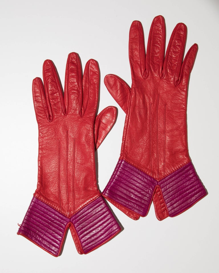 Yves Saint Laurent, circa 1970's red and purple color-block leather gloves featuring tonal stitching and lined in silk.  Size: Large  Length: 12