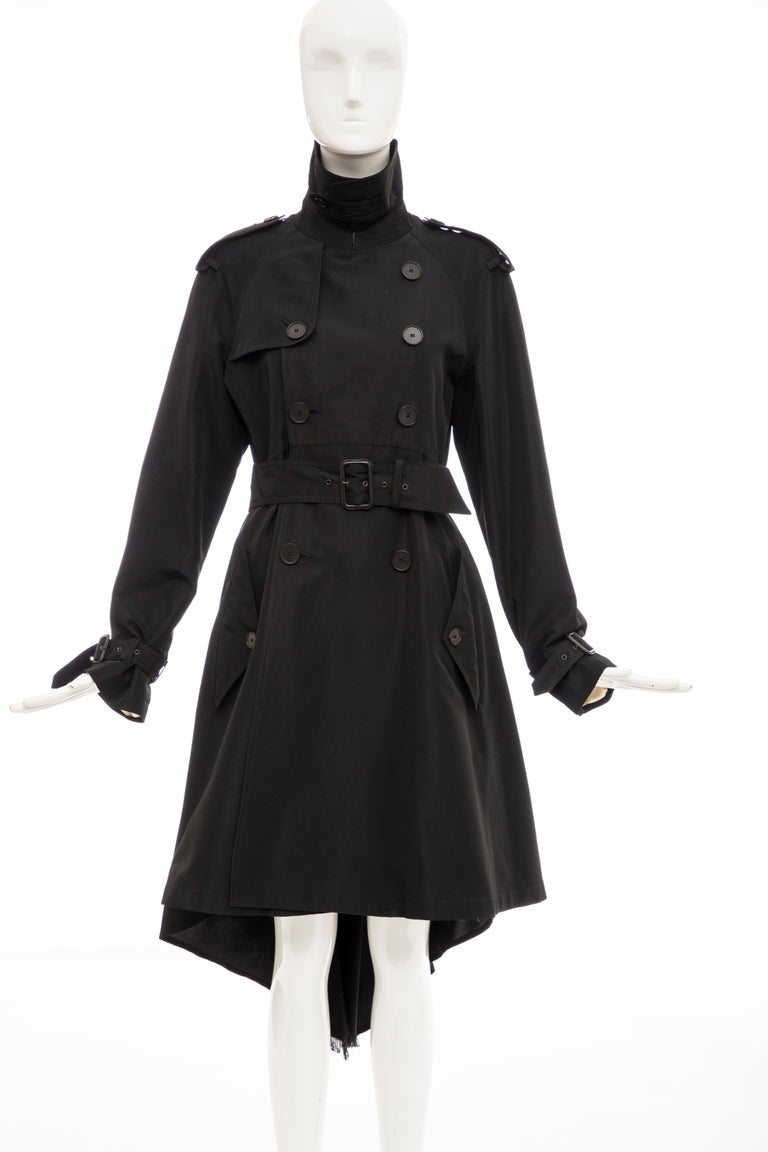 Jean Paul Gaultier, Fall 2007 black double-breasted trench coat with pointed collar, shoulder epaulets, dual flap pockets at sides, adjustable belt at waist featuring bow accent at back, fringe-trimmed high-low hem and button closures at front.